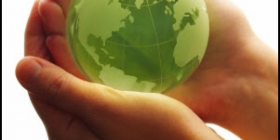A green small globe cradled in someone's hands